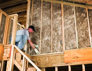 A man installing fiberglass batt insulation r value, cellulose insulation vs. fiberglass