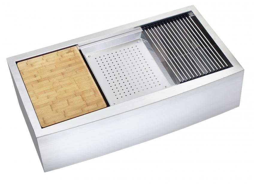 An apron-front sink from Lenova with a colander, grid drainer, and cutting board