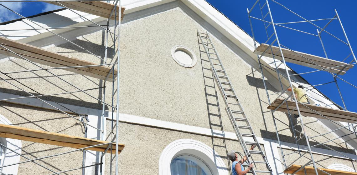 House builder working on stucco exterior